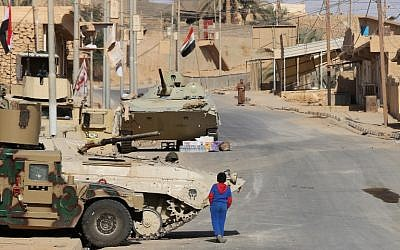 A boy walks past Iraqi forces vehicles in Rawa, after troops retook the Euphrates valley town from Islamic State group jihadists, November 18, 2017. (AFP/ Suleiman al-ANBARI)