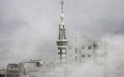 Smoke covers buildings following an air strike on the rebel-held besieged town of Arbin, in the Eastern Ghouta region on the outskirts of Damascus, on November 18, 2017. (AFP PHOTO / Amer ALMOHIBANY)