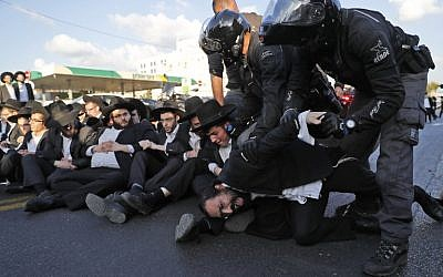 Police carry away ultra-Orthodox Jewish demonstrators as they disperse a protest against army conscription in the city of Bnei Brak, November 20, 2017. (AFP/Ahmad Gharabli)