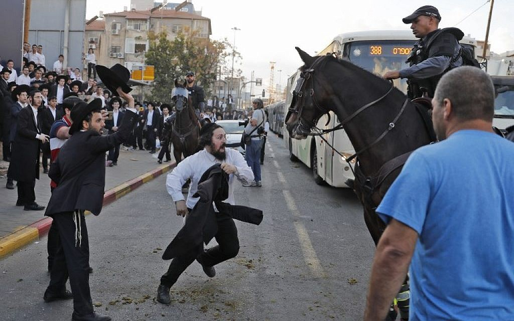 A horse-mounted police officer disperses ultra-Orthodox Jewish demonstrators during a protest against military conscription in Bnei Brak, a city near Tel Aviv, on November 20, 2017. (AFP Photo/Ahmad Gharabli)