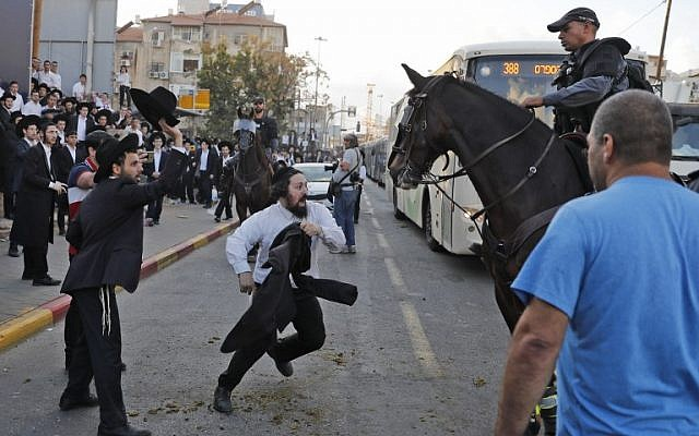 A horse-mounted Israeli security force member disperses Ultra-Orthodox Jewish demonstrators during a protest against Israeli army conscription in Bnei Brak, a city near Tel Aviv, on November 20, 2017. / AFP PHOTO / AHMAD GHARABLI