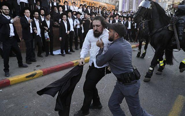 Israeli security forces carry away an ultra-Orthodox Jewish demonstrator as they disperse a protest against Israeli army conscription in Bnei Brak, a city near Tel Aviv, on November 20, 2017. (AFP PHOTO / AHMAD GHARABLI)