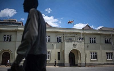 A man walks by Zimbabwe's parliament in Harare as Parliament prepares to start impeachment proceedings against President Robert Mugabwe, November 21, 2017.(AFP/Mujahid SAFODIEN)