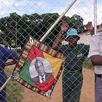 This file photo taken on April 10, 2000 shows a policeman and black squatters  guarding the farm of expelled white farmer Rob Marshell, in Mazowe, some 60 kilometers north of Harare. A portrait of President Robert Mugabe who encouraged the squatters to step up the occupations of white-owned farms, is seen on the fence. (AFP PHOTO / ALEXANDER JOE)