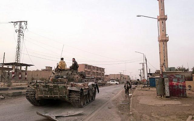 Le 20 novembre 2017, des membres des forces gouvernementales pro-syriennes conduisent un char dans une rue de la ville syrienne d'Albu Kamal. (AFP / STRINGER)
