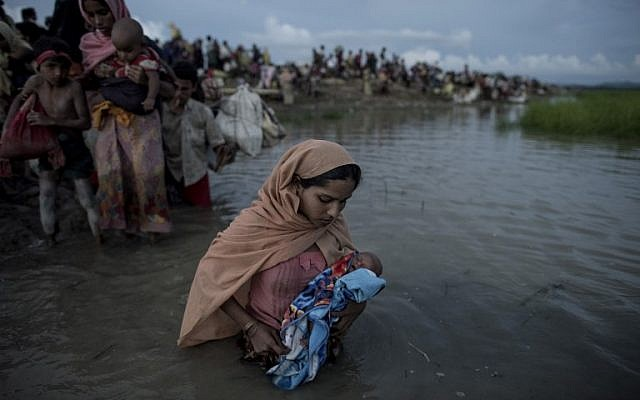 This photo taken on October 9, 2017 shows Rohingya refugees wading while holding a child after crossing the Naf river from Myanmar into Bangladesh in Whaikhyang on October 9, 2017. (AFP/Fred Dufour)