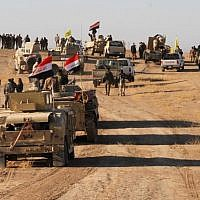 Iraqi forces, supported by members of the Hashed al-Shaabi (Popular Mobilization units), advance in the western desert in the northern Iraqi region of al-Hadar, 105 kilometers south of Mosul, on November 23, 2017, as they attempt to flush out remaining Islamic State group fighters (AFP/Stringer)