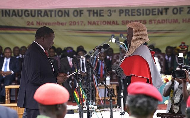 Newly sworn in as Zimbabwe's president Emmerson Mnangagwa (L) takes the oath of office at the national sports stadium on the outskirts of Harare, on November 24, 2017 during the Inauguration ceremony. (AFP PHOTO / Marco Longari)