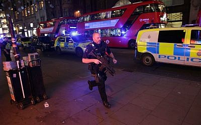 An armed policeman runs down Oxford Street in central London on November 24, 2017. (AFP/Daniel Leal-Olivas)