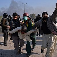 An injured activist from the Tehreek-i-Labaik Yah Rasool Allah Pakistan (TLYRAP) religious group is carried away from clashes with police in Islamabad on November 25, 2017. (AFP PHOTO / AAMIR QURESHI)