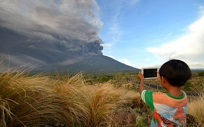 A boy takes pictures of Mount Agung as seen from Kubu sub-district in Karangasem Regency on Indonesia's resort island of Bali on November 26, 2017. (AFP PHOTO / SONNY TUMBELAKA)