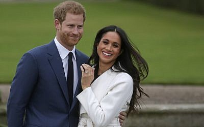 Britain's Prince Harry stands with his fiancée US actress Meghan Markle as she shows off her engagement ring whilst they pose for a photograph in the Sunken Garden at Kensington Palace in west London on November 27, 2017, following the announcement of their engagement. (AFP PHOTO / Daniel LEAL-OLIVAS)