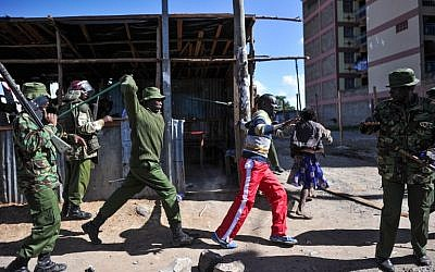 An anti-riot policeman beats a man with a stick as police flush out opposition supporters, who had taken cover in a shack to escape teargas, during demonstrations in the Umoja subururb of Nairobi, on November 28, 2017. (AFP Photo/Tony Karumba)