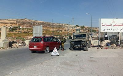 Israeli soldiers operate a checkpoint at the entrance to the village of Halhul, the hometown of a terrorist who rammed his car into two Israelis earlier in the day, on November 17, 2017. (Israel Defense Forces)