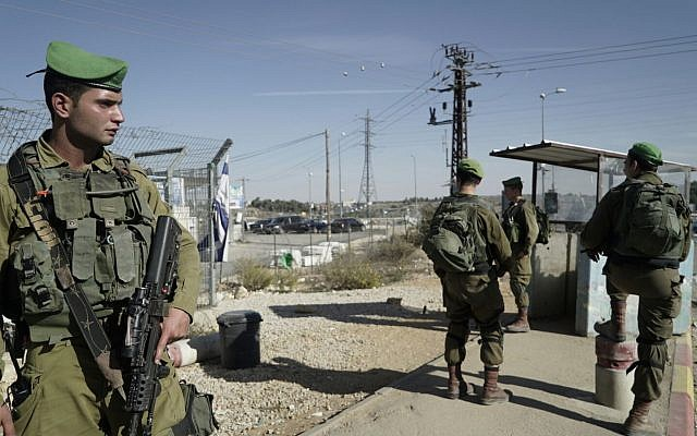 Israeli soldiers stand guard at the Gush Etzion Junction after a terrorist rammed his car into two Israelis there earlier in the day, on November 17, 2017. (Israel Defense Forces)