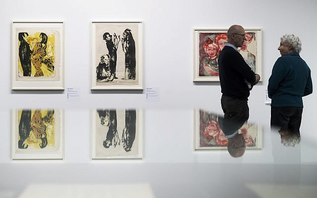 Two visitors in front of the paintings 'Junges Paar' (l), and 'Diskussion' of German painter Emil Nolde, in the exhibition 'Status Report  Gurlitt. degenerate art -- confiscated and sold'  in the Kunstmuseum in Bern, Switzerland, November 1, 2017. (Peter Klaunzer/Keystone via AP)