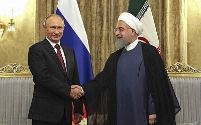 In this photo released by an official website of the office of the Iranian Presidency, Iran's President Hassan Rouhani, right, shakes hands with Russian President Vladimir Putin during their meeting at the Saadabad Palace in Tehran, Iran, Wednesday, Nov. 1, 2017. (Iranian Presidency Office via AP)