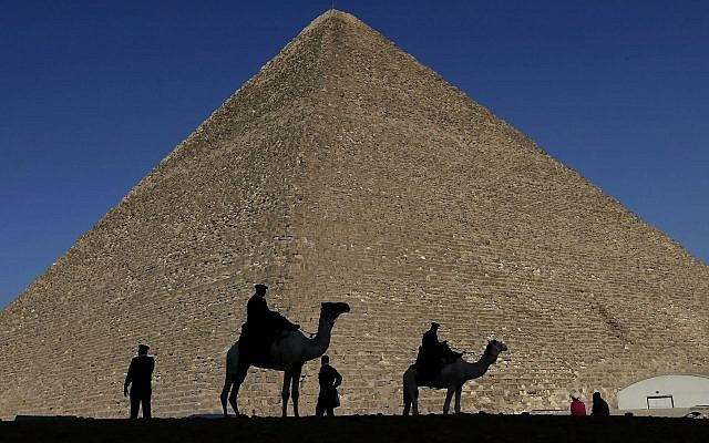 In this photo from December 12, 2012, policemen are silhouetted against the Great Pyramid in Giza, Egypt. (AP Photo/Hassan Ammar)