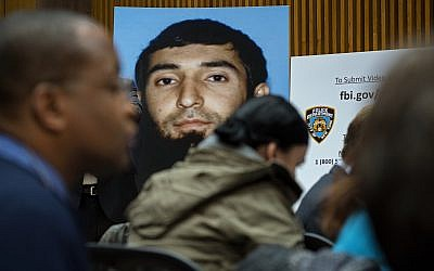 A photo of Sayfullo Saipov is displayed at a news conference at One Police Plaza Wednesday, Nov. 1, 2017, in New York.  Saipov is accused of driving a truck on a bike path that killed several and injured others Tuesday near One World Trade Center.  (AP Photo/Craig Ruttle)
