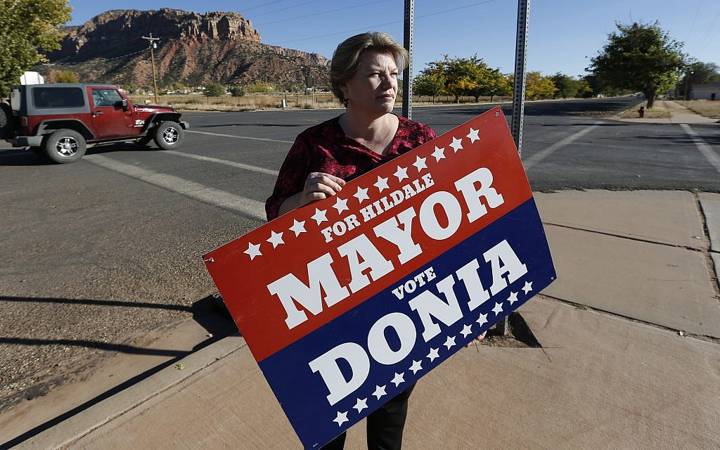 In this October 26, 2017 photo, Donia Jessop holds her mayoral campaign sign outside her store in Colorado City, Ariz. (AP Photo/Rick Bowmer)