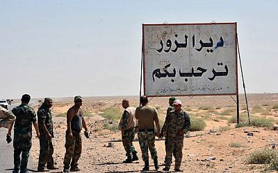 "This file photo released Sept. 3, 2017, by the Syrian official news agency SANA, shows Syrian troops and pro-government gunmen standing next to a sign in Arabic which reads, ""Deir el-Zour welcomes you,"" in the eastern city of Deir el-Zour, Syria. (SANA via AP, File)"
