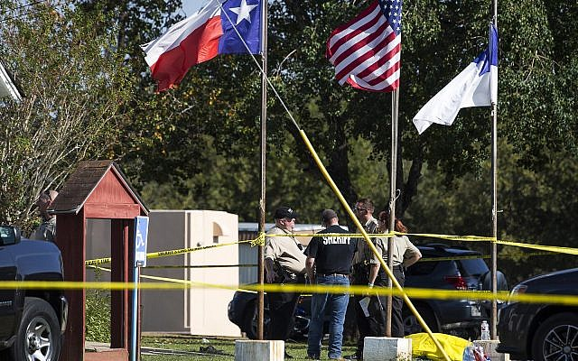 Law enforcement officials stand next to a covered body at the scene of a fatal shooting at the First Baptist Church in Sutherland Springs, Texas, on November 5, 2017. (Nick Wagner/Austin American-Statesman via AP)