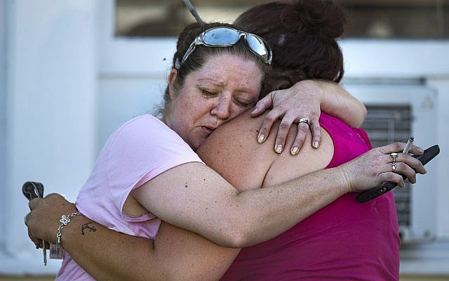 Carrie Matula embraces a woman after a fatal shooting at the First Baptist Church in Sutherland Springs, Texas, on November 5, 2017. (Nick Wagner/Austin American-Statesman via AP)