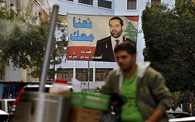 A street vendor stands in front of a poster of outgoing Prime Minister Saad Hariri, saying 'We are with you,' in Beirut, Lebanon, November 6, 2017. (AP Photo/Bilal Hussein)