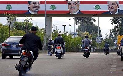 In this November 6, 2017 photo, a street is decorated with Lebanese flags and pictures of Interior Minister Nohad Machnouk, right, the late Prime Minister Rafik Hariri, center, and his son, outgoing Prime Minister Saad Hariri, in Beirut, Lebanon. (AP Photo/Bilal Hussein)