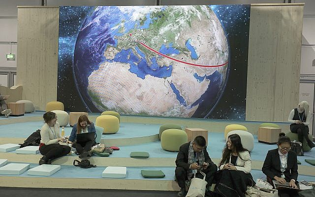 Participants at the World Climate Conference working in front of the depiction of a globe in Bonn, Germany, Tuesday, November 7, 2017. (Oliver Berg/dpa via AP)