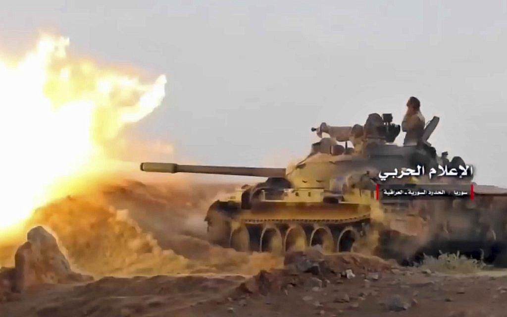 A frame grab from video provided by the government-controlled Syrian Central Military Media shows a tank firing on militants' positions on the Iraq-Syria border, November 8, 2017. (Syrian Central Military Media, via AP)