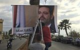 "Workers hang a poster of outgoing Prime Minister Saad Hariri with Arabic words that read, ""We are all Saad,"" on a seaside street in Beirut, Lebanon, November 9, 2017. (AP/ Hussein Malla)"