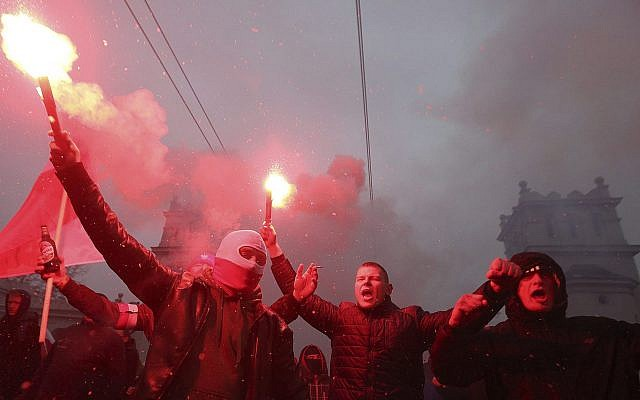 Nationalists burn flares as they march in large numbers through the streets of Warsaw to mark Poland's Independence Day, November 11, 2016, (AP Photo/Czarek Sokolowski, File)
