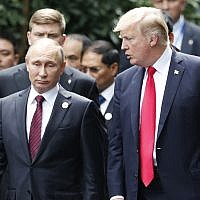 US President Donald Trump, right, and Russia's President Vladimir Putin talk during the family photo session at the APEC Summit in Danang, Vietnam Saturday, November 11, 2017. (Jorge Silva/Pool Photo via AP)