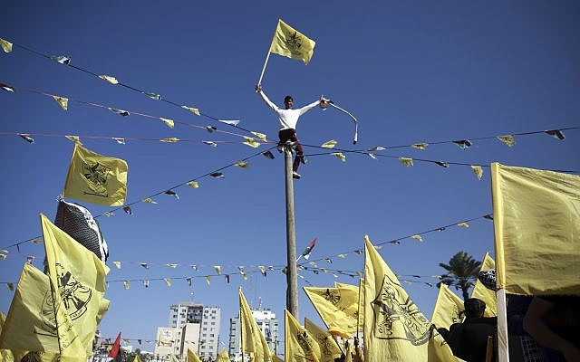 Palestinians wave yellow Fatah movement flags during a rally marking the 13th anniversary of the death of Fatah founder and Palestinian Authority leader Yasser Arafat, in Gaza City, Saturday, Nov. 11, 2017. (AP Photo/Khalil Hamra)