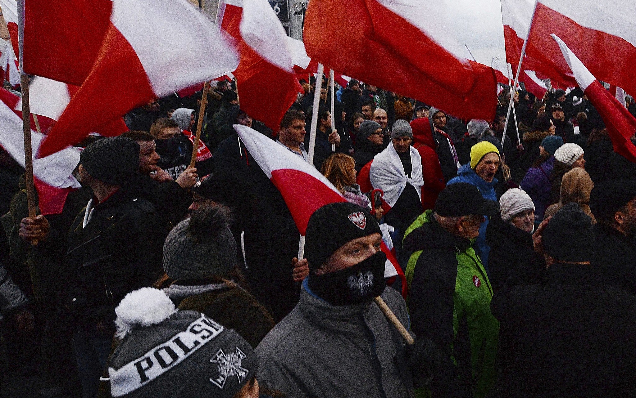 Demonstrators wave Polish flags during the annual march to commemorate Poland's National Independence Day in Warsaw Saturday Nov. 11 2017. Thousands of nationalists marched in Warsaw on Poland's Independence Day holiday taking part in an eve