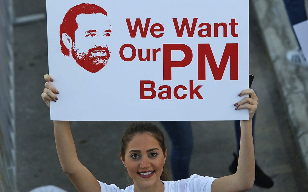 A Lebanese woman holds a placard supporting the outgoing Lebanese Prime Minister Saad Hariri to return from Saudi Arabia during the Beirut Marathon, in Beirut, Lebanon, November 12, 2017. (AP Photo/Hassan Ammar)
