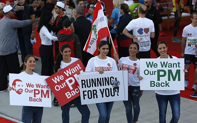 Lebanese women hold placards supporting the outgoing Lebanese Prime Minister Saad Hariri to return from Saudi Arabia during the Beirut Marathon in Beirut, Lebanon, November 12, 2017. (AP Photo/Hassan Ammar)