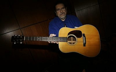 Garry Shrum, a music memorabilia specialist at Heritage Auctions, displays an acoustic guitar that belonged to Bob Dylan in Dallas, on October 13, 2017. (AP Photo/LM Otero)