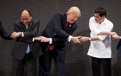 "US President Donald Trump, center, reacts as he does the ""ASEAN-way handshake"" with Vietnamese Prime Minister Nguyen Xuan Phuc, left, and Philippine President Rodrigo Duterte on stage during the opening ceremony at the ASEAN Summit at the Cultural Center of the Philippines, November 13, 2017, in Manila, Philippines. (AP/Andrew Harnik)"