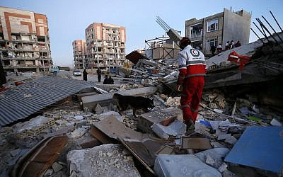 Illustrative image provided by the Iranian Students News Agency, ISNA, shows a rescue worker searches debris for survivors with his sniffing dog after an earthquake at the city of Sarpol-e-Zahab in western Iran, on November 13, 2017. (Pouria Pakizeh/ISNA via AP)