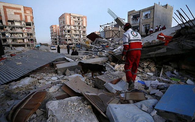 A rescue worker searches debris for survivors with his sniffing dog after an earthquake at the city of Sarpol-e-Zahab in western Iran, November 13, 2017. (Pouria Pakizeh/ISNA via AP)