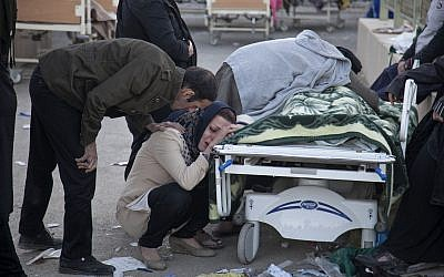 Relatives weep over the body of an earthquake victim,  in Sarpol-e-Zahab, western Iran, November 13, 2017. (Farzad Menati/Tasnim News Agency via AP)