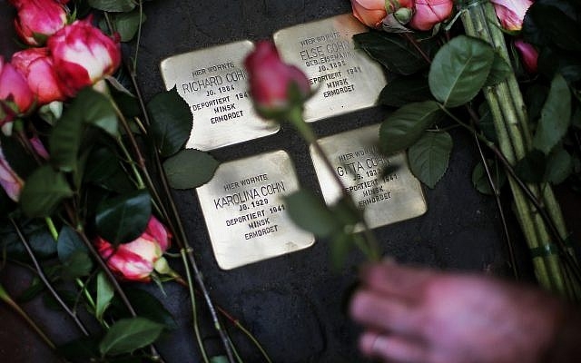 "Roses are laid on four ""Stolpersteine"" (stumbling blocks) for Karolina Cohn and her family in Frankfurt, Germany, Monday, Nov. 13, 2017. (AP Photo/Michael Probst)"