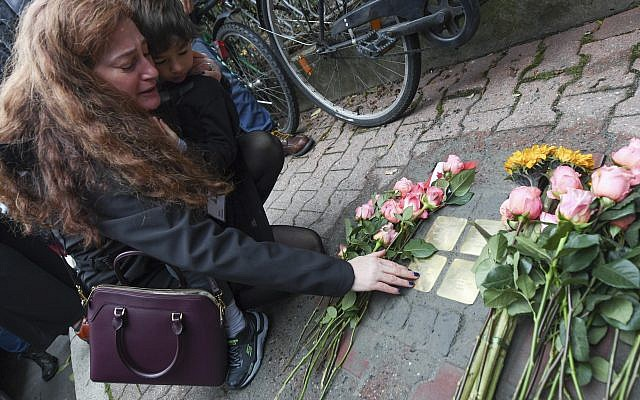 """Mandy Eisemann from Dickerson, Maryland. with her son Levi (4), relatives of the Cohn family, places flowers at  four """"Stolpersteine"""" (stumbling blocks) for Karolina Cohn and her family in Frankfurt, Germany, November 13, 2017. (Arne Dedert/dpa via AP)"""