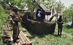 In this April 1996 photo, two fighters from the Lebanese terror group Hezbollah stand near Katyusha rockets in the southern village of Ein Qana, Lebanon. (AP Photo/Mohammed Zaatari)