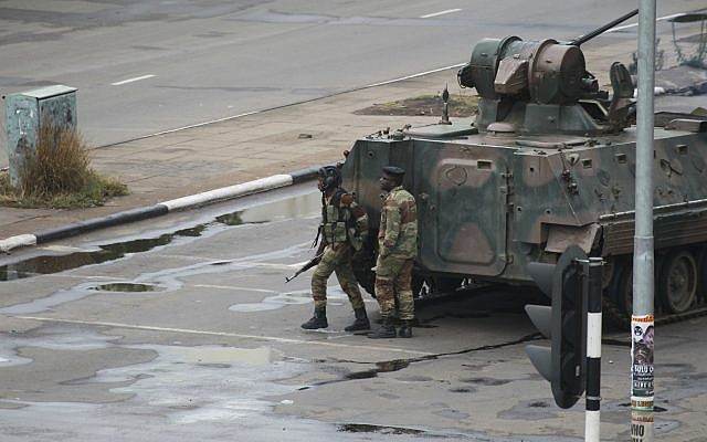 A military armored personnel carrier is seen with armed soldiers on the road leading to President Robert Mugabe's office in Harare, Zimbabwe Wednesday, Nov. 15, 2017. (AP Photo/Tsvangirayi Mukwazhi)