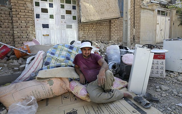 An earthquake survivor sits next to his belongings, which were recovered from debris in Sarpol-e-Zahab in western Iran, November 15, 2017. (AP/Vahid Salemi)