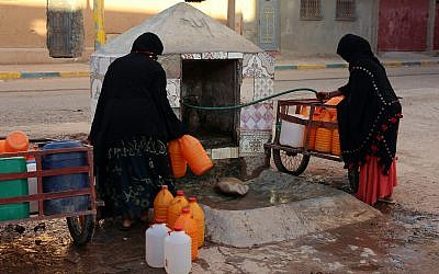 Moroccan women filling up containers with water from a hose, in Zagora, southeastern Morocco, October 9, 2017. (AP Photo/Issam Oukhouya, File)
