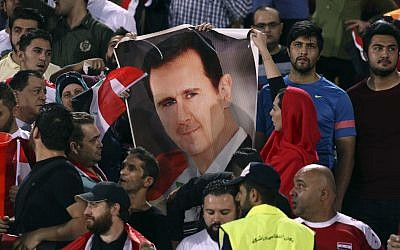 Syrian soccer fans hold a portrait of their president, Bashar Assad, before their match with Iran during a Round 3 - Group A World Cup qualifier at the Azadi Stadium in Tehran, Iran, September 5, 2017. (AP Photo/Vahid Salemi)